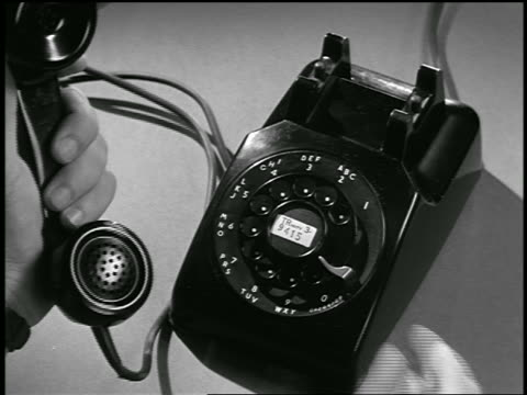 b/w 1954 close up hand of man dialing rotary telephone / industrial - landline phone stock videos and b-roll footage