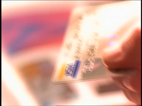 close up hand of man handing Visa credit card to woman