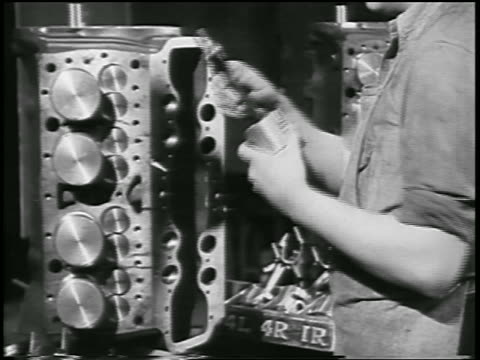 vidéos et rushes de b/w 1932 close up hand of man inserting pistons into engine (?) in ford car factory / industrial - ford