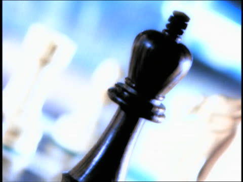canted close up hand of man knocking over chess piece + putting down his piece - チェス点の映像素材/bロール