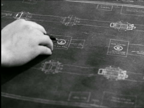 B/W 1944 close up hand of man pointing on blueprints for machine gun mount / industrial