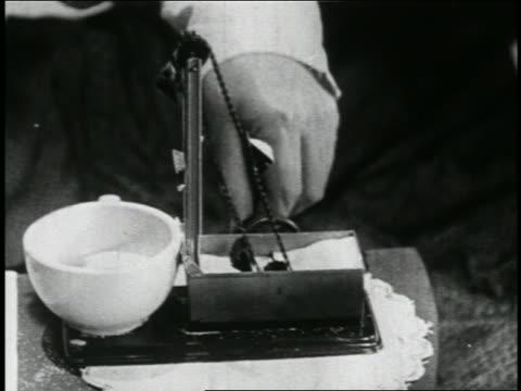 vídeos de stock e filmes b-roll de b/w 1923 close up hand of man pulling chain releasing sugar into coffee cup / short - só um rapaz