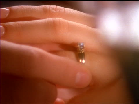 close up hand of man putting diamond ring on woman's ring finger - engagement stock videos and b-roll footage