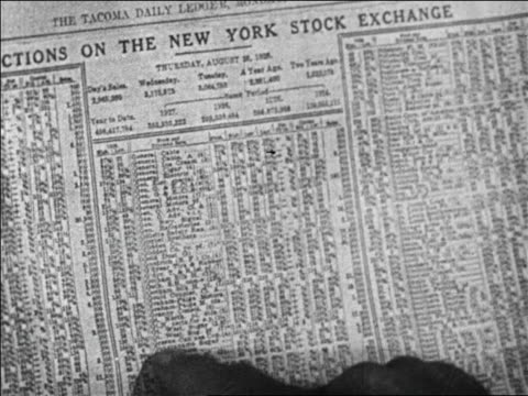 b/w 1929 close up hand of man running down figures in financial pages / newsreel - broadsheet stock videos and b-roll footage