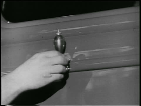 b/w 1932 close up hand of man using device to paint stripe on car body in ford car factory / industrial - 1932 stock videos & royalty-free footage