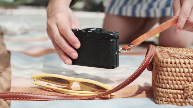 vídeos de stock, filmes e b-roll de close-up mão de mulher alinhamento tapete de pano piquenique na praia.relax férias de verão - toalha de praia