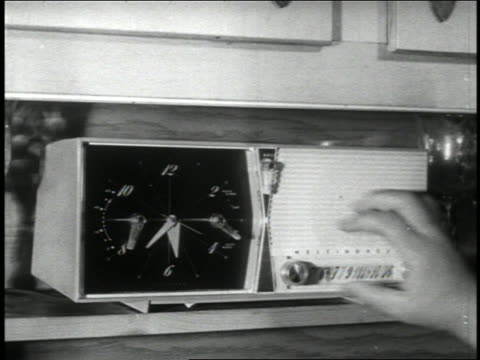vidéos et rushes de b/w 1950 close up hand of woman moving switch on clock radio on shelf - poste de radio