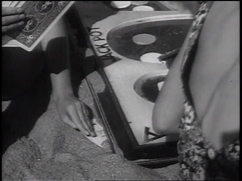 B/W 1937 close up hand of woman pulling card from sand in card game on beach / newsreel