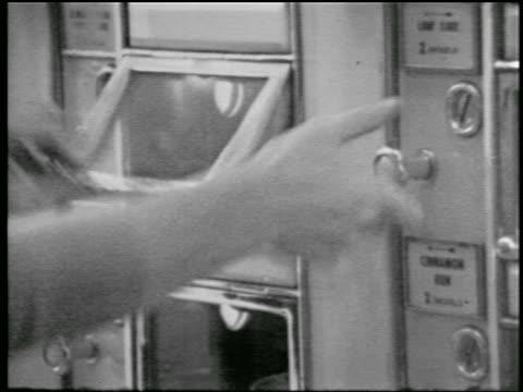 b/w 1957 close up hand of woman turning knob + lifting door of vending machine in dine-o-mat - 1957 bildbanksvideor och videomaterial från bakom kulisserna