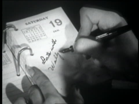 "b/w 1947 close up hand of  woman writing in desk calendar ""date with wally"" - terminplanung stock-videos und b-roll-filmmaterial"