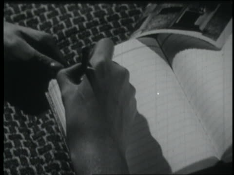 b/w 1953 close up hand of woman writing in diary - schreiben stock-videos und b-roll-filmmaterial