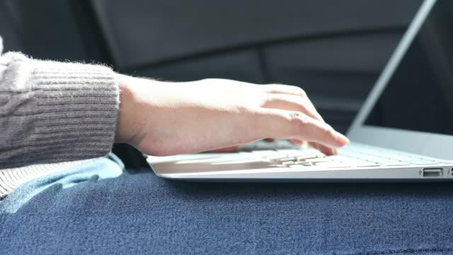車の中のコンピューターを使用している女性の手を閉じる - 人の背中点の映像素材/bロール