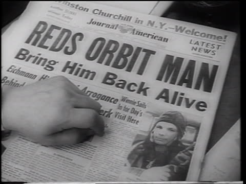 b/w 1961 close up hand on newspaper with reds orbit man headline photo of yuri gagarin - 1961 stock-videos und b-roll-filmmaterial