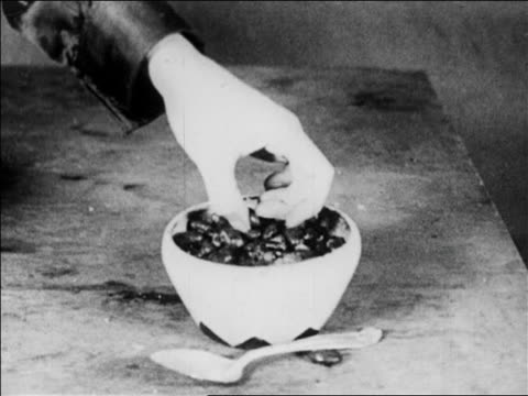 B/W 1920 close up hand picking up bean from bowl / feature
