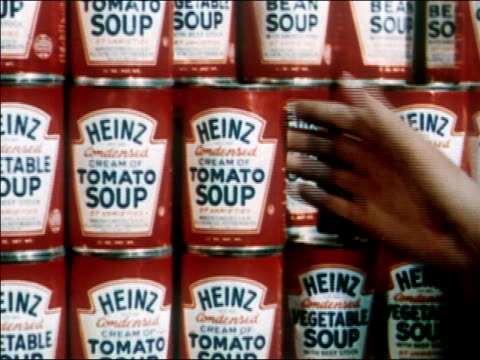 1951 Close up hand picking up can of Heinz cream of tomato soup from display / AUDIO