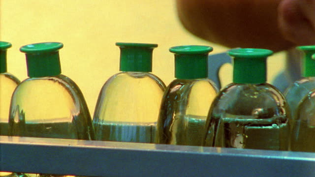 close up hand placing bottles on assembly line - shampoo stock videos & royalty-free footage