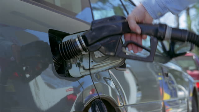 close up hand placing nozzle of gas pump into gas tank of car and turning on pump / vermont - dejaover点の映像素材/bロール