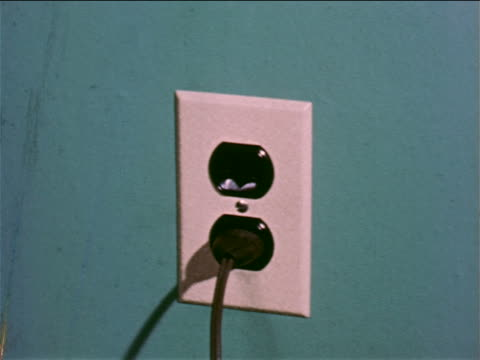 1957 close up hand plugging cord into electrical outlet / industrial