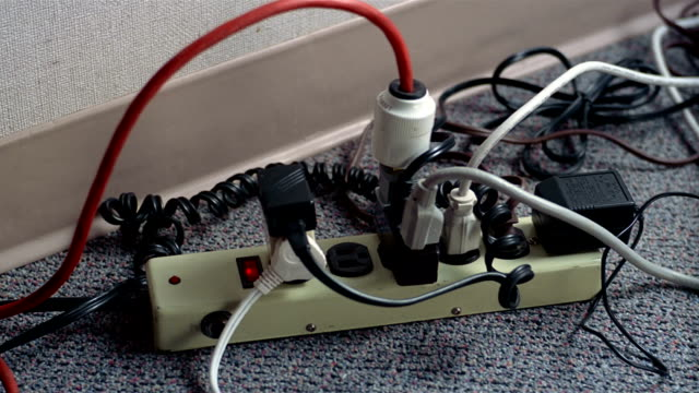 Close up hand plugging three prong cord into power strip crowded with other plugs