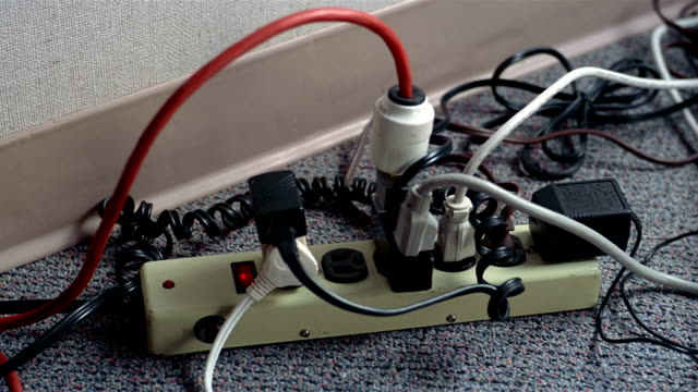 stockvideo's en b-roll-footage met close up hand plugging three prong cord into power strip crowded with other plugs / lights going out - stroomuitval