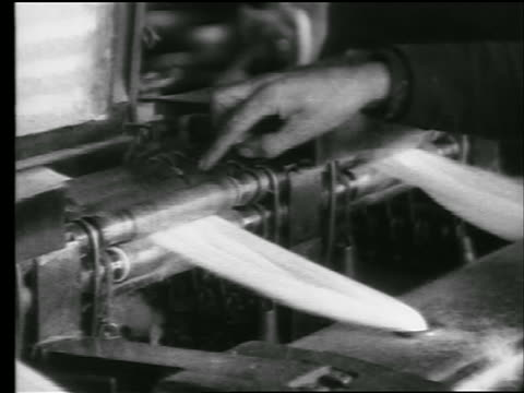 b/w 1922 close up hand points to rollers in machine in cotton mill / newsreel - textile mill stock videos & royalty-free footage
