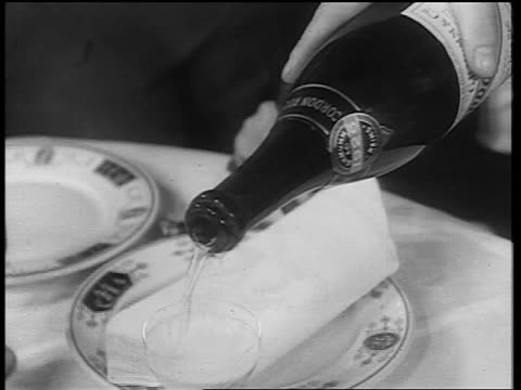b/w 1933 close up hand pouring from bottle into glass on table / end of prohibition - 1933年点の映像素材/bロール