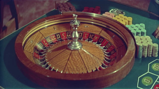 close up hand puts ball in spinning roulette wheel / meet me in las vegas (1956) - roulette stock videos and b-roll footage