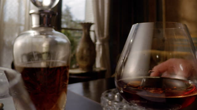 close up hand putting cigar on ashtray and picking up snifter of brandy/ dolly shot brandy being poured into snifter - brandy snifter stock videos and b-roll footage