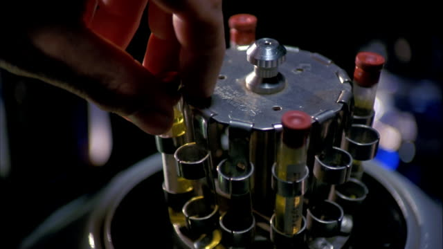 close up hand putting test tube filled with liquid in centrifuge / centrifuge spinning - centrifuge stock videos & royalty-free footage