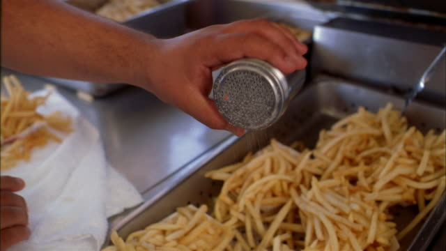 close up hand seasoning baskets of french fries w/salt in fast food restaurant kitchen - unhealthy eating 個影片檔及 b 捲影像