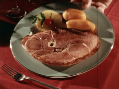 1964 close up hand serving plate of ham with pineapple + potatoes on the side / industrial - boiled stock videos and b-roll footage