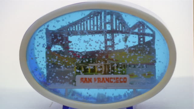 Close up hand setting down shaken San Francisco snowglobe with Golden Gate Bridge and trolley car inside