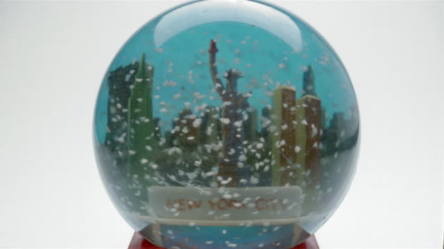 Close up hand setting down shaken snowglobe with New York City and Statue of Liberty scene inside