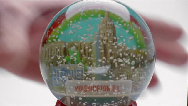 Close up hand setting down shaken snowglobe with Washington D.C. and Capitol building scene inside