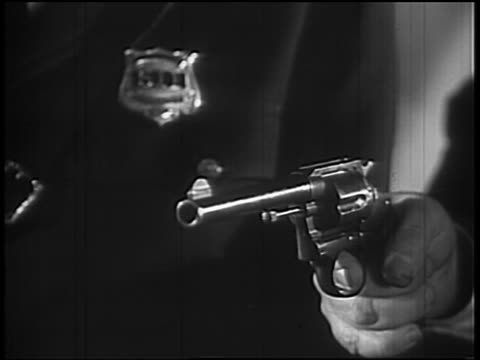 b/w 1932 close up hand shooting revolver / policeman's chest with badge in background - arma da fuoco video stock e b–roll