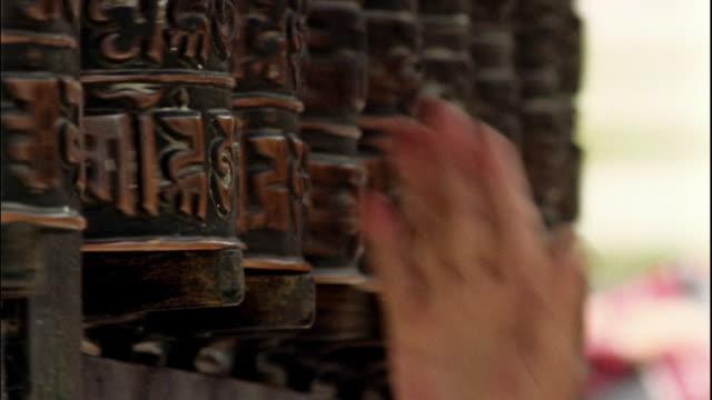 Close up hand spinning prayer wheels at Swayambhunath Temple / Kathmandu, Nepal