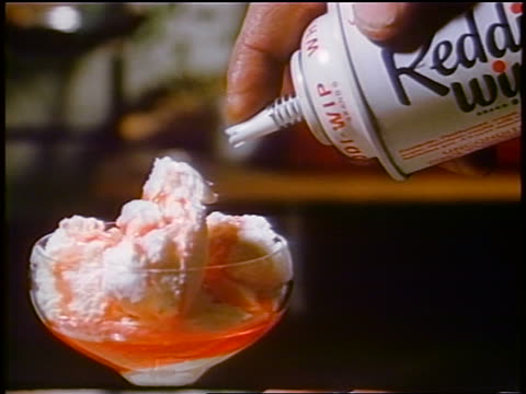 1958 close up hand spraying whip cream from can onto ice cream / newsreel - cream stock videos and b-roll footage