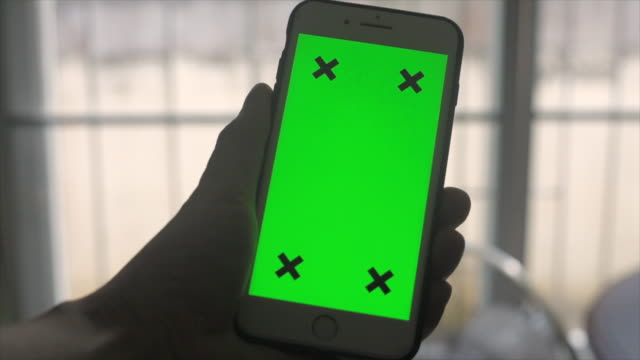 Close up hand touching smartphone with green screen display.