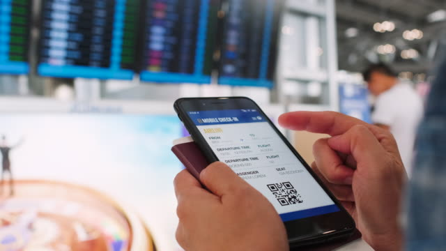 close up hand traveler woman check in flight with mobile app at airport - biglietto aereo video stock e b–roll