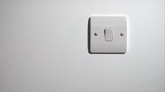 Close up hand turning off light switch