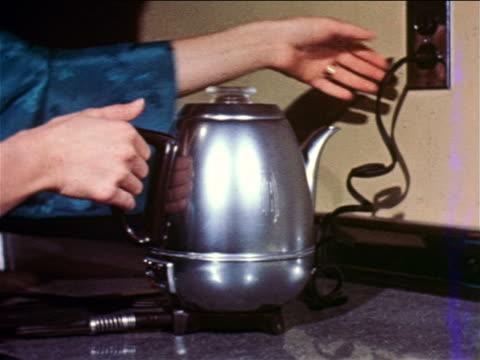 1957 close up hand unplugging electric metal coffee porcolator sitting on counter / industrial - bricco per il caffè video stock e b–roll