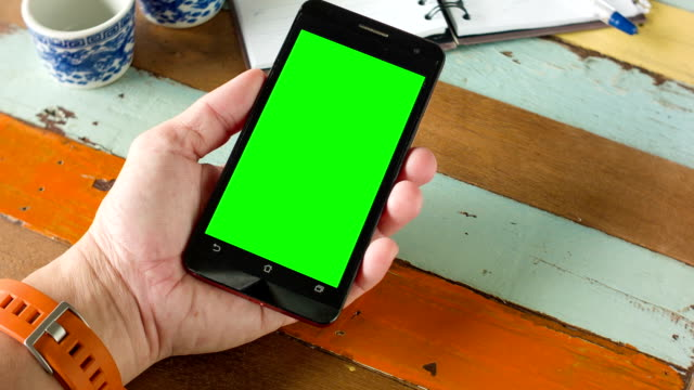 Close up hand using smart phone with blank green screen for chroma key