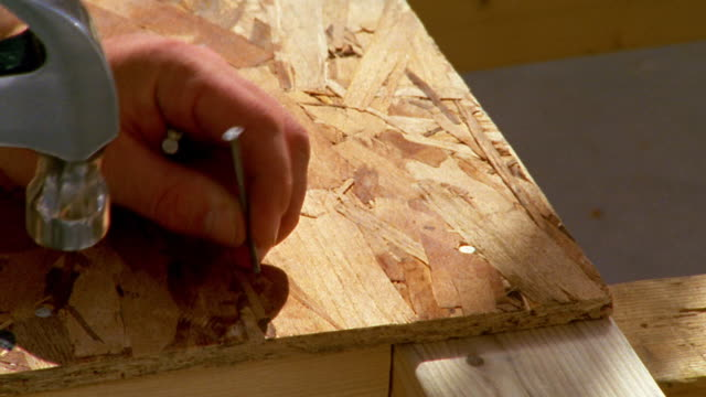 Close up hand with hammer pounding nail into chip board