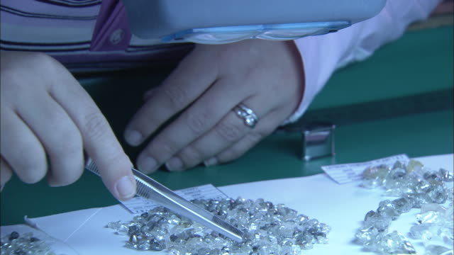 Close Up hand-held - A diamond sorter with tweezers peers at diamonds through magnifying goggles. / South Africa