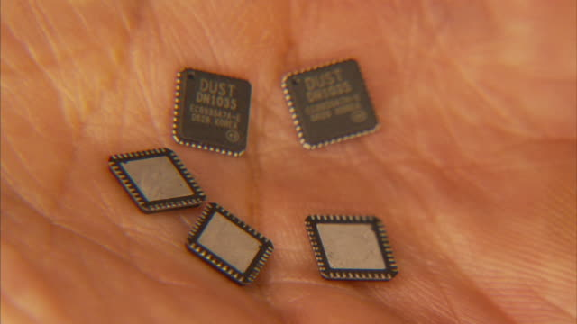 Close Up hand-held - A human hand holds small sensors known as smart dust chips.