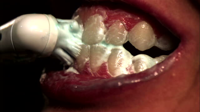 close up, hand-held - a woman uses an electric toothbrush / usa - toothbrush stock videos & royalty-free footage