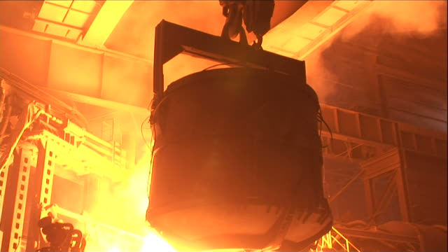 vídeos de stock, filmes e b-roll de close up hand-held push-in - a crane lowers a bucket over a furnace of molten steel / claymont, delaware  - fornalha
