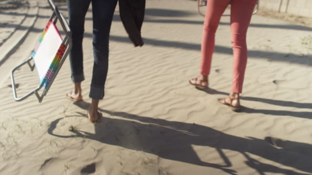 close up handheld tracking shot of black womens feet walking through sand on the beach - tracking shot stock videos & royalty-free footage