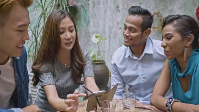 食堂での携帯電話でソーシャル メディアを共有する友人のハンドヘルド ビデオを閉じる - マレーシア点の映像素材/bロール