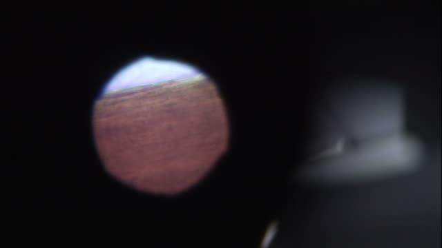 vídeos y material grabado en eventos de stock de close up hand-held zoom-out - a microscope enlarges details on a piece of evidence. / usa - magnificación